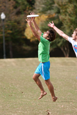 ultimate: Atlanta, GA USA - October 27, 2012:  Two unidentified young men battle each other to catch a frisbee in  an Ultimate Frisbee game between two teams in Piedmont Park. Editorial