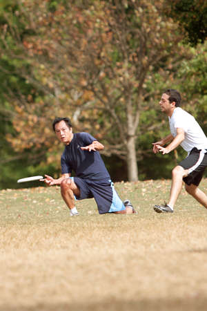 Atlanta, GA USA - October 27, 2012:  An unidentified young male kneels to throw a frisbee during an Ultimate Frisbee game between two teams in Piedmont Park.