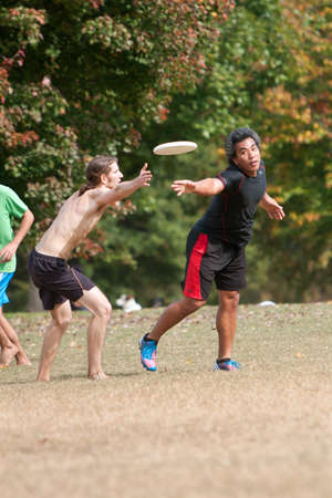 frisbee: Atlanta, GA USA - October 27, 2012:  Two unidentified men compete in an Ultimate Frisbee game between two teams in Piedmont Park.
