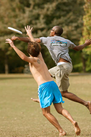 Atlanta, GA USA - October 27, 2012:  Two unidentified men battle each other to catch a frisbee in  an Ultimate Frisbee game between two teams in Piedmont Park. 報道画像