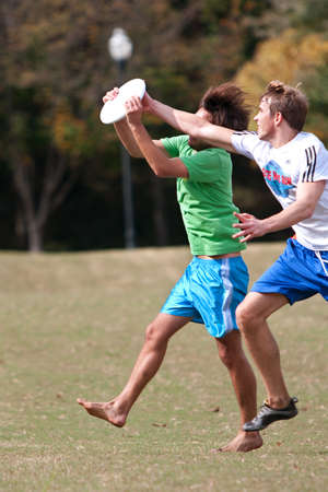 Atlanta, GA USA - October 27, 2012:  Two unidentified young men battle each other to catch a frisbee in  an Ultimate Frisbee game between two teams in Piedmont Park. 新聞圖片