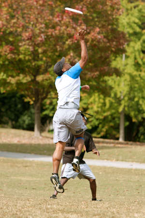Atlanta, GA, USA - October 27, 2012:  An unidentified young male jumps to catch a frisbee during an Ultimate Frisbee game between two teams in Piedmont Park.