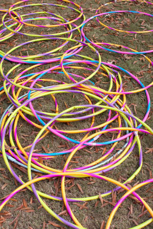 Atlanta, GA, USA - October 27, 2012:  Several brightly colored hula hoops lying on the ground form overlapping circular patterns.  The hula hoops were available for kids to play with at a pumpkin carving event at Piedmont Park.