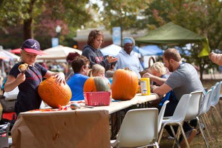 carving pumpkin: Atlanta, GA, EE.UU. - 27 de octubre de 2012: Familias tallar y pintar calabazas en un evento de talla de calabaza en Piedmont Park, el s�bado antes de Halloween.