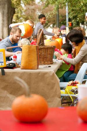 carving pumpkin: Atlanta, GA, EE.UU. - 27 de octubre de 2012: Los padres ayudan a sus hijos peque�os tallar y pintar calabazas en un evento de talla de calabaza en Piedmont Park, el s�bado antes de Halloween.
