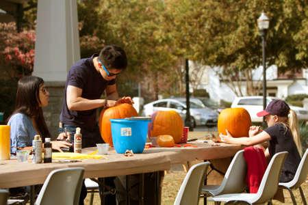 carving pumpkin: Atlanta, GA, EE.UU. - 27 de octubre de 2012: Personas no identificadas tallar y pintar calabazas en un evento de talla de calabaza en Piedmont Park, el s�bado antes de Halloween.