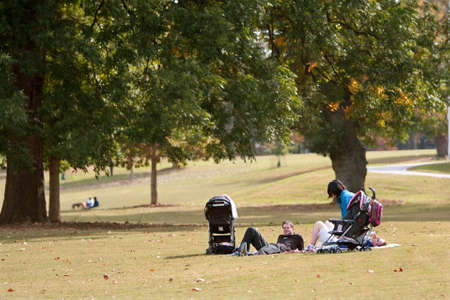 Atlanta, GA USA - October 27, 2012:  Young parents relax on a blanket with their baby strollers parked close by, in a wide open field in Piedmont Park.