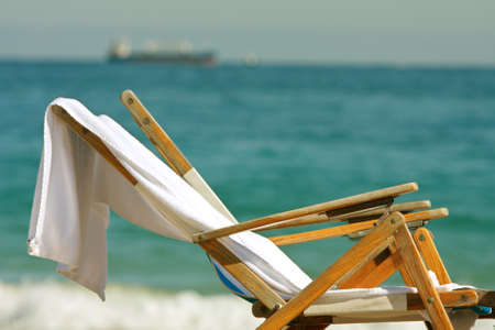 Two wooden deck chairs with towels slung over them sit on Florida beach
