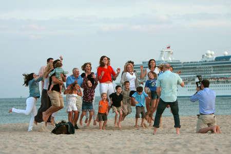 포트. 로더데일, 플로리다, 미국 - 2012년 12월 29일 : 포트의 해변에 준비된 사진을 위해 포즈를 취하는 동안 알 수없는 가족이 공중에서 점프. 크리스마