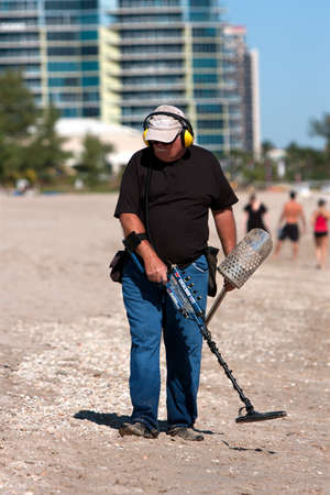 Ft. Lauderdale, FL, USA - December 27, 2012:  An unidentified senior man combs a Florida beach with a metal detector, over the Christmas holidays.