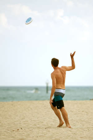 ft lauderdale: Ft. Lauderdale, FL, USA - December 29, 2012:  An unidentified man throws a frisbee on the beach of a Ft. Lauderdale resort over the Christmas holidays.