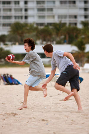 Ft. Lauderdale, FL, USA - December 29, 2012:  An unidentified teenage boy catches the ball while another boy defends, in a touch football game on the beach of a Ft. Lauderdale hotel.