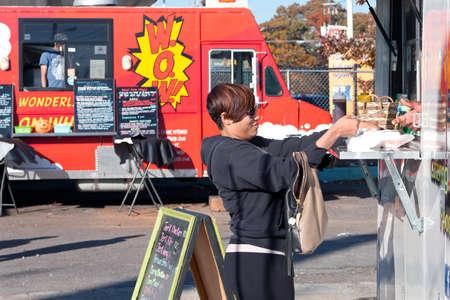 food industry: Atlanta, GA - November 17, 2012:  An unidentified customer buys food from a high-end food truck at the Atlanta Food Truck Park.
