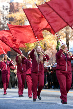 Atlanta, GA, USA - December 1, 2012:   The flag corps of a high school marching band twirls their flags while performing in the annual Atlanta Christmas parade in downtown Atlanta. Editorial