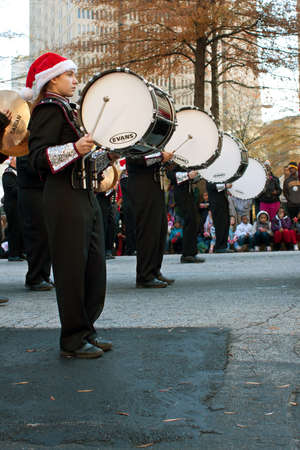 Atlanta, GA, USA - December 1, 2012:   Bass drummers in a high school marching band bang their drums while perfomring in the annual Atlanta Christmas parade in downtown Atlanta. Editorial