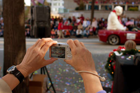 larger than life: Atlanta, GA, USA - December 1, 2012:   A womans hands hold a point and shoot camera as she captures moments from the annual Atlanta Christmas parade in downtown Atlanta. Editorial
