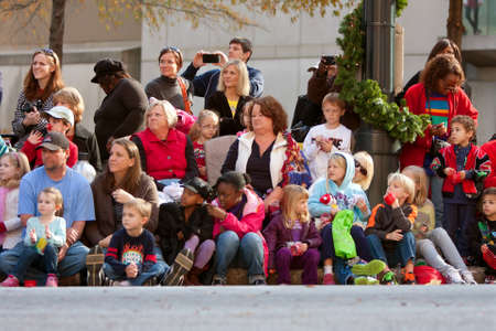 Atlanta, GA, USA - December 1, 2012:  Spectators watch from the sidewalk and street curb as the Atlanta Christmas parade takes place down Peachtree Street in downtown Atlanta.