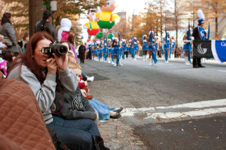 Atlanta, GA, USA - December 1, 2012:  Spectators watch from the street curb as the Atlanta Christmas parade takes place on Peachtree Street in downtown Atlanta.