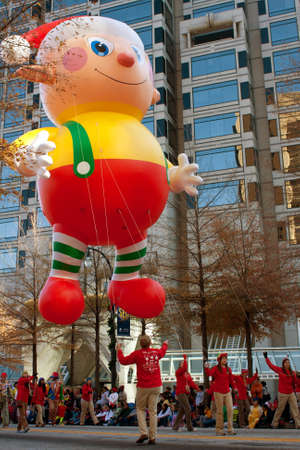Atlanta, GA, USA - December 1, 2012:  Workers use ropes to guide a huge float along the parade route in the annual Atlanta Christmas parade in downtown Atlanta. Editorial