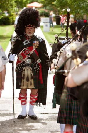 Atlanta, GA, USA - May 25, 2012: A drum major leads a local bagpipes group in performing at the GREAT festival, a spring festival celebrating Great Britain and the United Kingdom, on the grounds of Oglethorpe University.