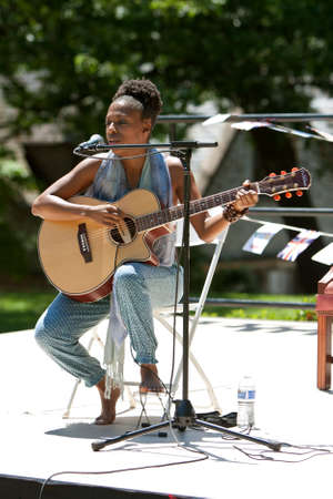 Atlanta, GA, USA - May 25, 2012:  A female singer plays acoustic guitar and sings at the GREAT festival, a spring festival celebrating Great Britain and the United Kingdom.