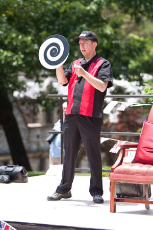 Atlanta, GA, USA - May 25, 2012:  A magician performs on stage for the crowd attending the GREAT festival, a spring festival celebrating Great Britain and the United Kingdom.
