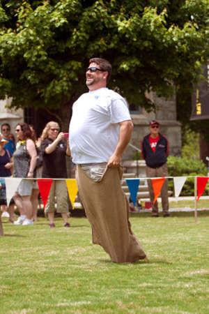 fr�hlingsfest: Atlanta, GA, USA - 25. Mai 2012: Ein unbekannter Mann konkurriert in einem Sack-Rennen auf dem gro�en Fest, einem Fr�hlingsfest feiert Gro�britannien und das Vereinigte K�nigreich.