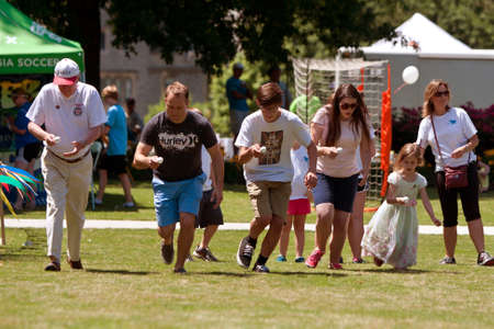 Atlanta, GA, USA - May 25, 2012:  Several people run in the egg and spoon race at the GREAT festival, a spring festival celebrating Great Britain and the United Kingdom. 報道画像