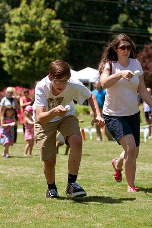 Atlanta, GA, EE.UU. - 25 de mayo de 2012: Dos personas se concentran durante la ejecución de la carrera del huevo y la cuchara en el gran festival, un festival de primavera que celebra la Gran Bretaña y el Reino Unido. Foto de archivo - 20062349