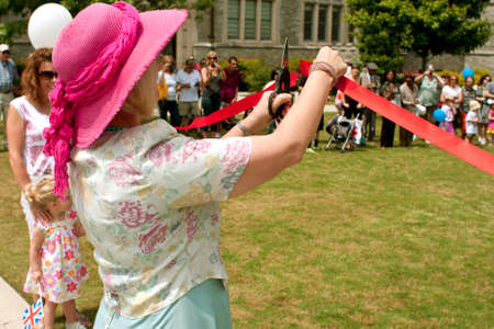 Atlanta, GA, USA - May 25, 2012:  An unidentified woman cuts the ribbon to open the GREAT festival, an event celebrating Great Britain and the United Kingdom.