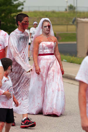 Atlanta, GA, USA - June 8, 2013:  A blood soaked zombie bride walks in the Atlanta Zombie Run, a 5K run and walk where hundreds of runners dodged zombies during the 5K race. Stock Photo - 20372127