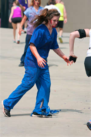 Atlanta, GA, USA - June 8, 2013:  A female zombie nurse wearing blood-soaked scrubs, chases a runner in the Atlanta Zombie Run. Hundreds of runners ran around zombies in the 5K race.