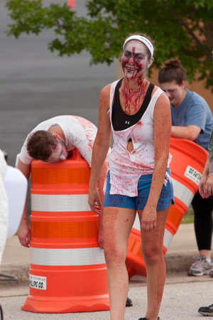 running nose: Atlanta, GA, USA - June 8, 2013:  A blood soaked zombie laughs and waits for runners to get closer, as they move through the course at the Atlanta Zombie Run. Hundreds of runners dodged zombies in the 5K race.