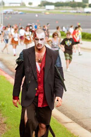 Atlanta, GA, EE.UU. - 8 de junio de 2013: Un zombi masculino que lleva un traje hecho jirones, se desprende de la multitud después de perseguir a los corredores en el Zombie Run Atlanta. Cientos de corredores esquivaron zombies en la carrera de 5 km. Foto de archivo - 20372123
