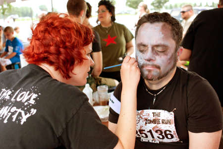 gets: Atlanta, GA, USA - June 8, 2013:  An unidentified man gets a zombie makeover after the Atlanta Zombie Run, a 5K run and walk where hundreds of runners dodged zombies during the race. Editorial
