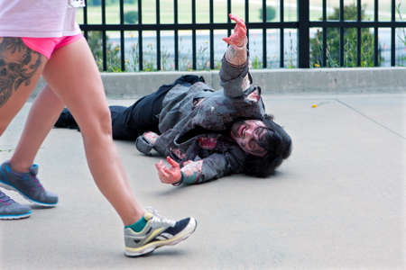 Atlanta, GA, USA - June 8, 2013:  A zombie lying on the asphalt reaches for women passing by in the Atlanta Zombie Run.  Hundreds of runners ran around zombies in the 5K race. Editorial