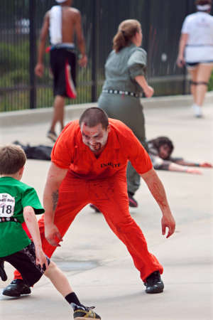 Atlanta, GA, USA - June 8, 2013:  A zombie wearing orange inmate coveralls, tries to catch a boy running in the Atlanta Zombie Run.  Hundreds of runners ran around zombies in the 5K race.