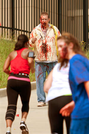 Atlanta, GA, USA - June 8, 2013:  A blood soaked zombie waits for runners to get closer, as they move through the course at the Atlanta Zombie Run. Hundreds of runners dodged zombies in the 5K race.