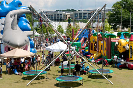 Atlanta, GA, USA - June 29, 2013:  Parents watch kids bungee jump on trampolines and play in the children's area at the Old Fourth Ward Arts Festival in Atlanta. Banco de Imagens - 20739034