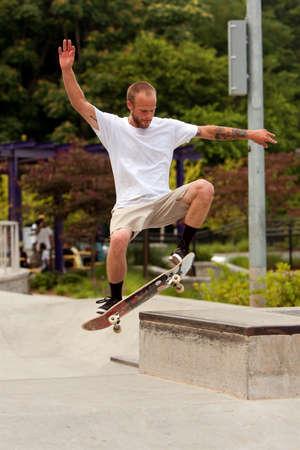 tatoos: Atlanta, GA, USA - June 29, 2013:  A young man practices a skateboard trick at the Old Fourth Ward Skateboard Park in Atlanta.