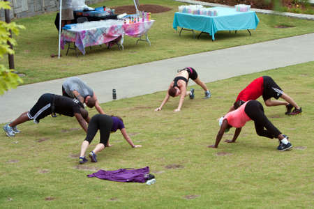 Atlanta, GA, USA - June 29, 2013:  Men and women stretch after working out in a fitness boot camp on a grassy field in the old 4th ward of Atlanta. Editorial