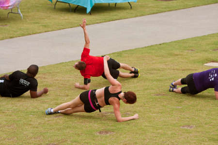 hard: Atlanta, GA, USA - June 29, 2013:  Men and women work out in a fitness boot camp on a grassy field in the old 4th ward of Atlanta. Editorial
