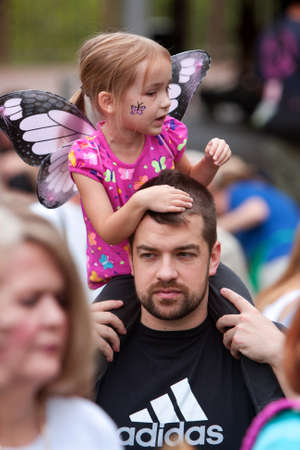 Roswell, GA, USA - July 13, 2013:  A dad carries his daughter on his shoulders so she can see the release of the butterflies at the Chattahoochee Nature Centers summer butterfly festival.