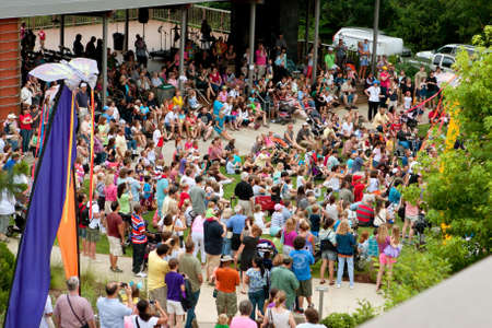 large crowd: Roswell, GA, USA - July 13, 2013:  A large crowd of people stand and sit on the lawn, waiting for the release of the butterflies at the Chattahoochee Nature Centers summer butterfly festival. Hundreds of people attended the annual event. Editorial