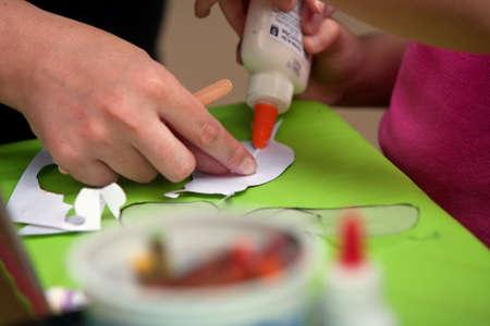 resistol: Roswell, GA, EE.UU. - 13 de julio de 2013: Primer plano de la mano de una madre ayudando a su hija pegamento los artes y los artes proyectan juntos, en el festival de la mariposa de Nature Center Chattahoochee.