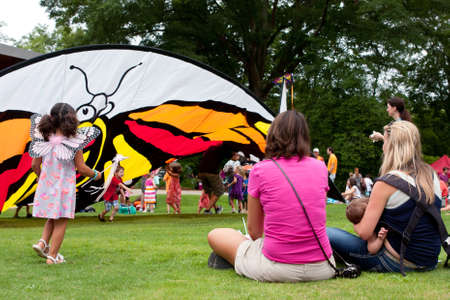 Roswell, GA, USA - July 13, 2013:  Mothers sit and watch their kids play around a butterfly tent at the Chattahoochee Nature Center's Butterfly Festival.  Hundreds of people attended the two-day event.  Stock Photo - 21008139