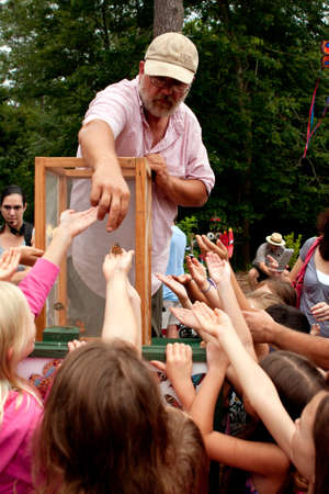 Roswell, GA, USA - July 13, 2013:  An unidentified man releases butterflies from a box, as a crowd of youthful hands reach for them at the Chattahoochee Nature Center's Butterfly Festival. Stock Photo - 21099885