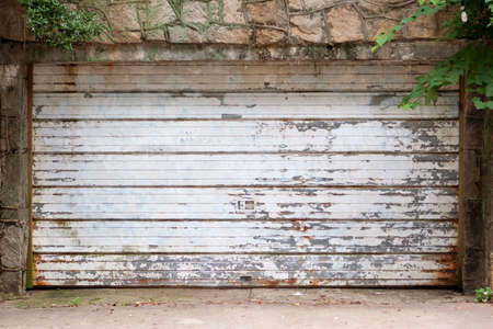 chipped paint: Old garage door with rust and chipped paint Stock Photo