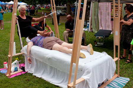 Atlanta, GA, USA - July 27, 2013:  A woman receives an Ashiatsu barefoot massage at the 3rd Annual Atlanta Ice Cream Festival at Piedmont Park.  The event was free and open to the public. Фото со стока - 21368382