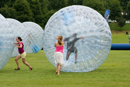 large ball: Atlanta, GA, USA - July 27, 2013:  Women push young people around in rolling zorbs at the 3rd Annual Atlanta Ice Cream Festival at Piedmont Park.  The event was free and open to the public.